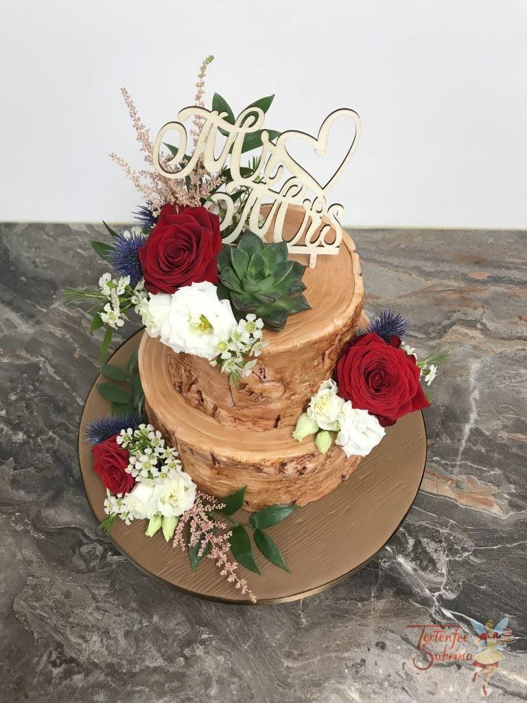 Hochzeitstorte - Blumen auf Baumstumpf. Der Tortenrand wurde wie eine Rinde modeliert und angemalt und Blumenschmuck ziert die Torte.