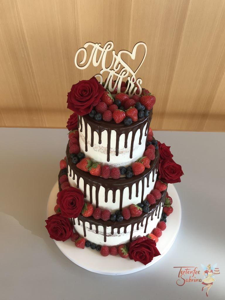 Hochzeitstorte - Blumen und Beeren, dieser Drip Cake mit dunkler Schokolade wurde mit roten Rosen und verschiedenen Beeren verziert.