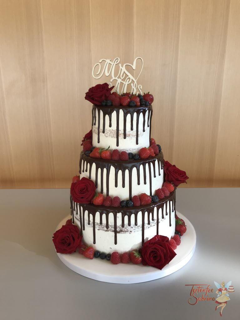 Hochzeitstorte - Blumen und Berren, dieser Drip Cake mit dunkler Schokolade wurde mit roten Rosen und verschiedenen Berren verziert.