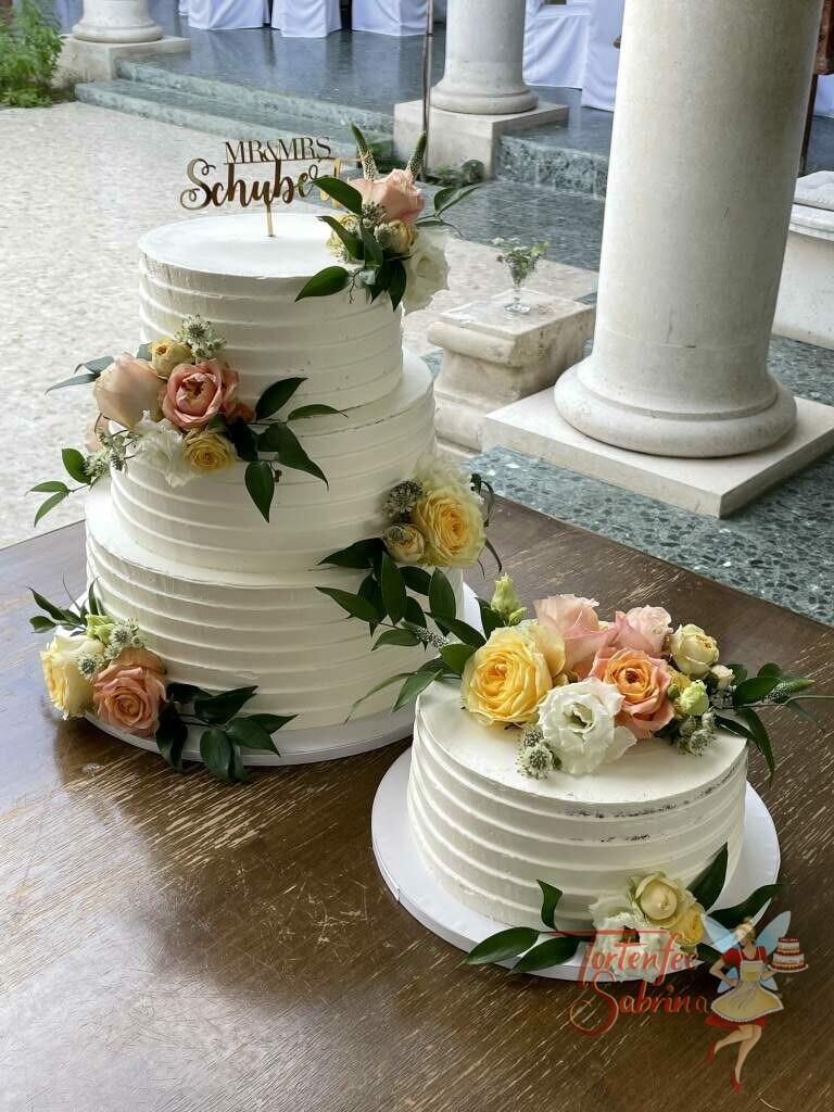 Hochzeitstorte - Blumen mit Rillen und einem goldenen Cake-Topper. Die Torte wurde mit Rosen in den Farben gelb, rosa und weiß verziert.