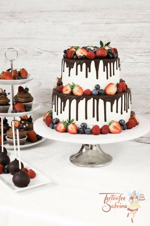 Hochzeitstorte - Ein Traum aus Früchten, hier wurde die Hochzeitstorte mit einem schokoladigen Drip und verschiedenen Beeren verziert.