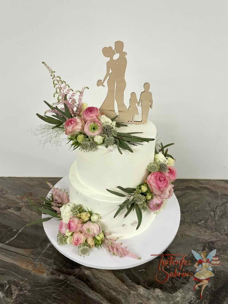 Hochzeitstorte - Familie mit Blumen zeigt eine Torte mit einem schönen Holz-Topper und schönen Rosen in weiß und rosa.