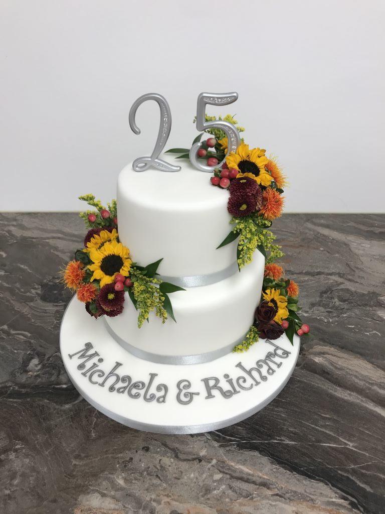 Hochzeitstagstorte - Silberne 25ig ziert die obere Torte in Form eines Cake Toppers. Die Torte wurde ebenfalls mit echten Blumen dekoriert.
