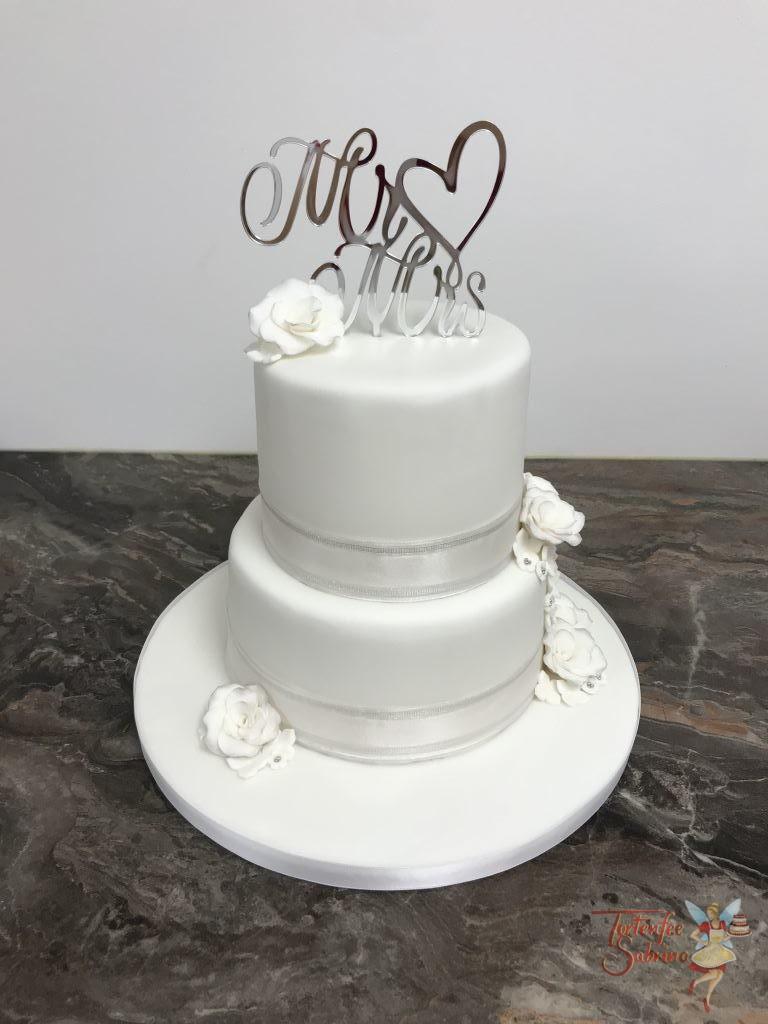 Hochzeitstorte - Weiß mit Rosen und einem schönen Band. Den oberen Abschluß bildet ein schöner Cake Topper in silber.