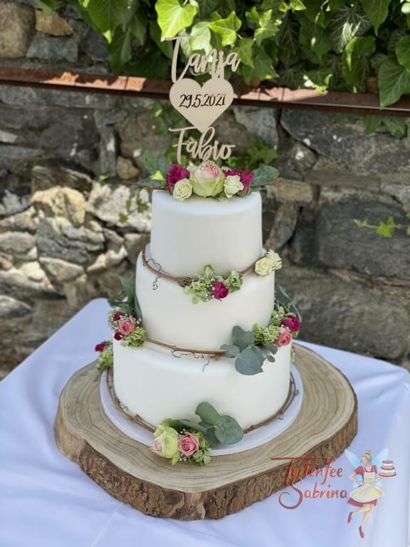 Hochzeitstorte - Zarter Blumenring mit verschieden färbigen Rosen auf einer Weinrebe, oben auf der Torte ist ein persönlicher Topper.