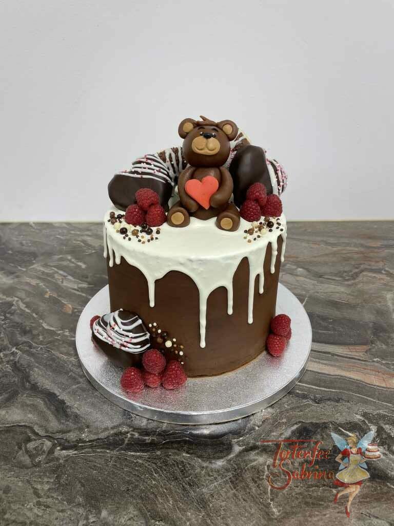 Jahrestagstorte - Bär mit Schokoherzen, hier sitzt der Marzipan-Bär auf einer Decke aus weißer Schokolade mit seinem roten Herzen.