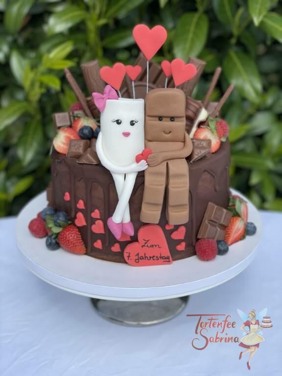 Jahrestagstorte - Kinderriegel mit Herz, auf diesem Drip-Cake sitzen Milky und Schoki umgeben von vielen Süßigkeiten und Früchten.