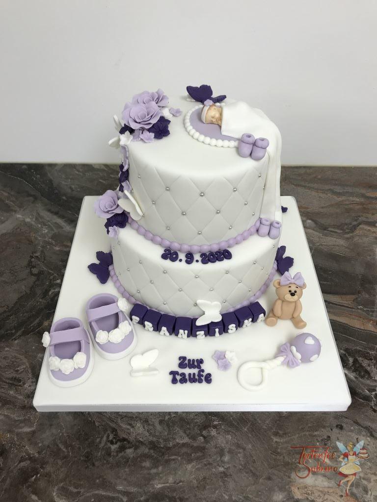 Tauftorte - Baby in lila und violett mit Schuhen und Blumen. Den Rand der beiden Torten ziert ein Rautenmuster und Perlen.