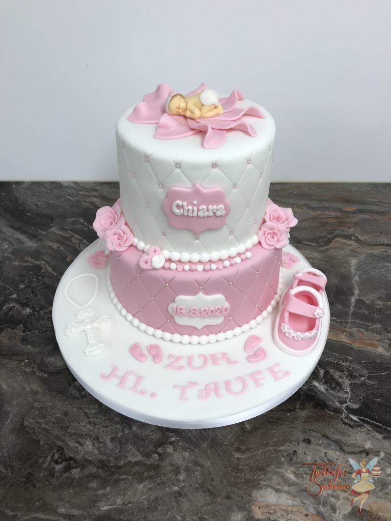 Tauftorte - Baby in rosa Blüte. Die Torte ist 2-stöckig mit Rautenmuster und Perlen verziert. Dekoriert mit Schuhen, Blumen und Kreuz.