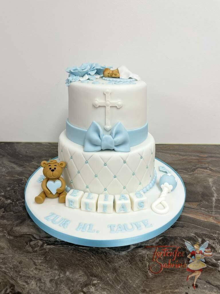Tauftorte - Baby mit blauen Rosen, weiters auf der Torte sitze ein Bär mit blauem Herz. Ebenso ist ein Kreuz und ein Schleife auf der Torte.