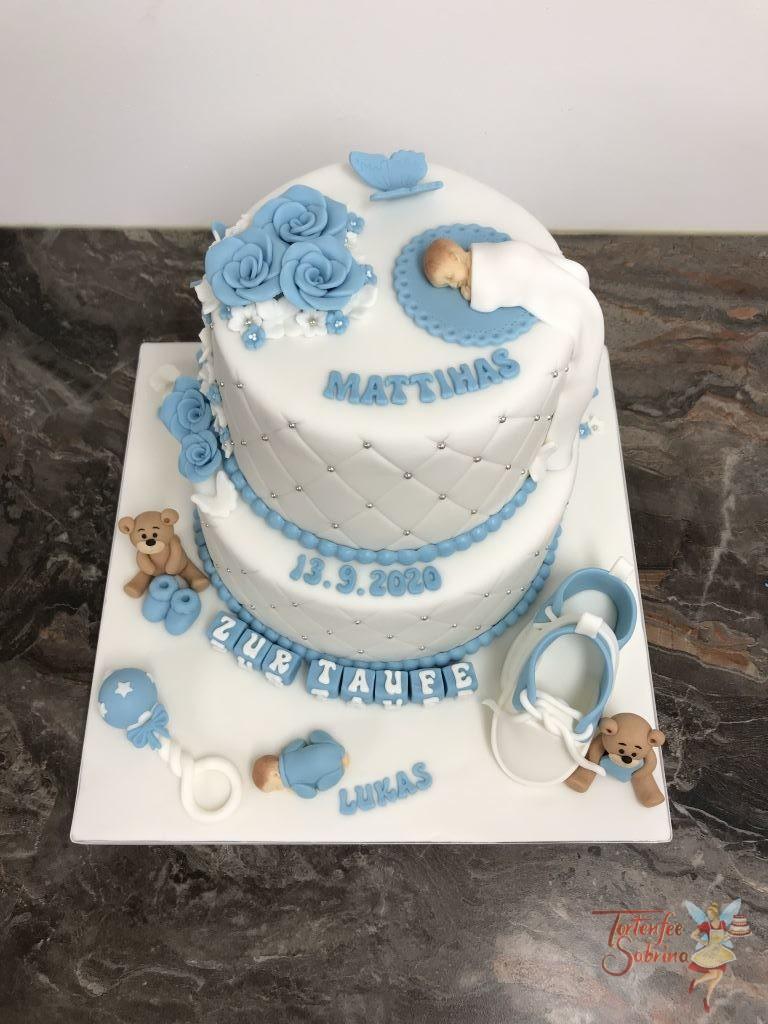Tauftorte - Baby mit blauen Rosen. Die Torte wurde einem Rautenmuster und Perlen verziert und mit Bärchen, Schmetterlingen, Schuhen und Blumen.