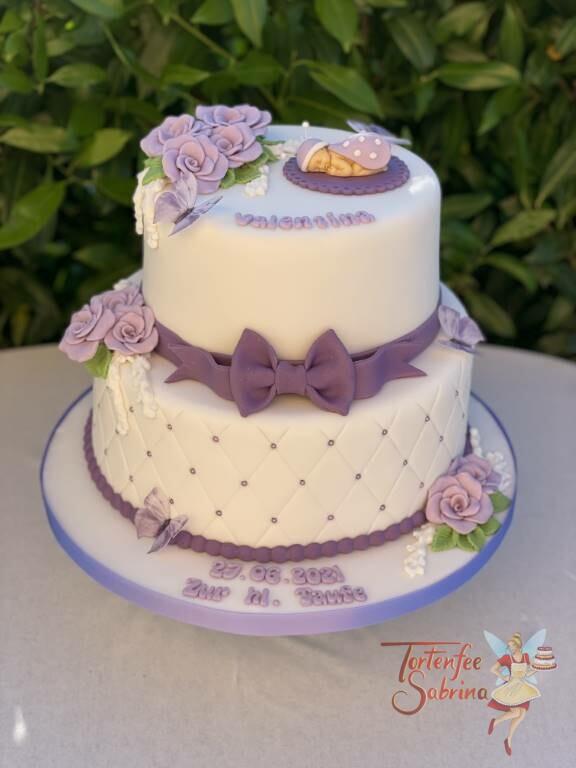 Tauftorte - Baby mit lila Marienkäferflügel, liegt auf der Torte auf einem Deckchen. Ebenfalls auf der Torte Rosen.