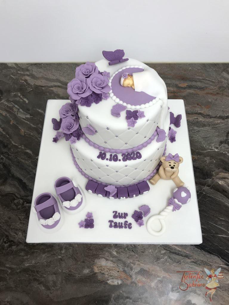 Tauftorte - Baby mit lila und violetten Blumen. Diese Torte wurde mit einem Bär, Rassel und Schüchen verziert.