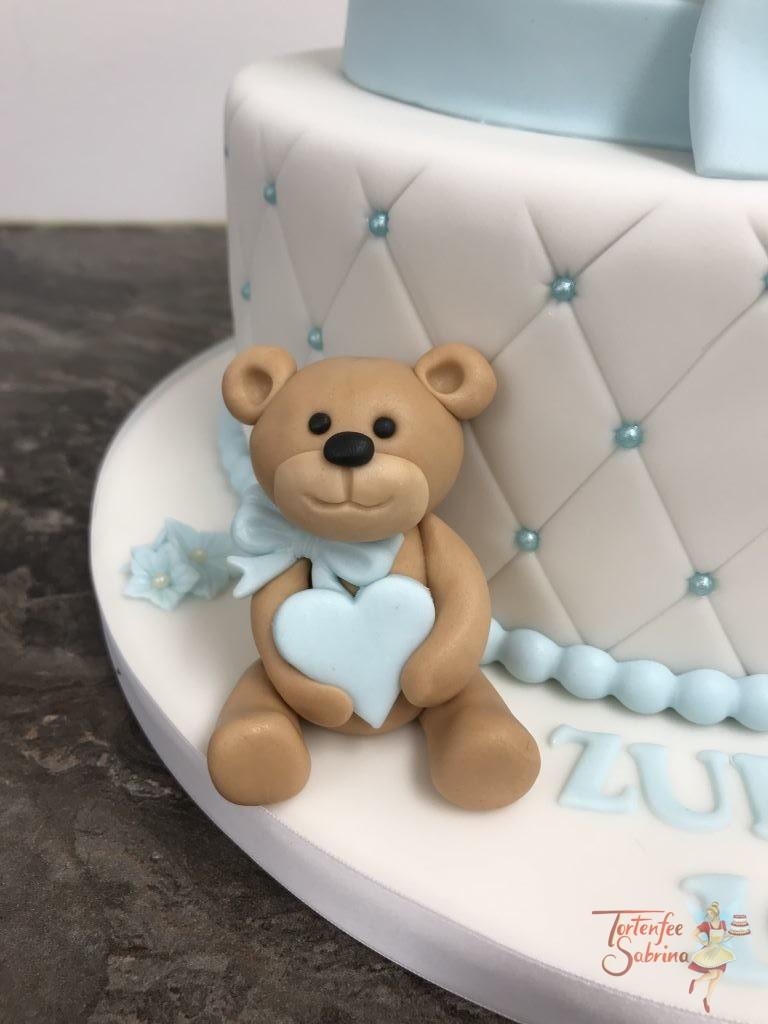 Tauftorte - Baby unter der Kuscheldecke. Diese 2-stöckige Torte wurde mit Rautenmuster und Perlen versehen. Dekoriert mit Bär, Rassel, Blumen und Schleife.