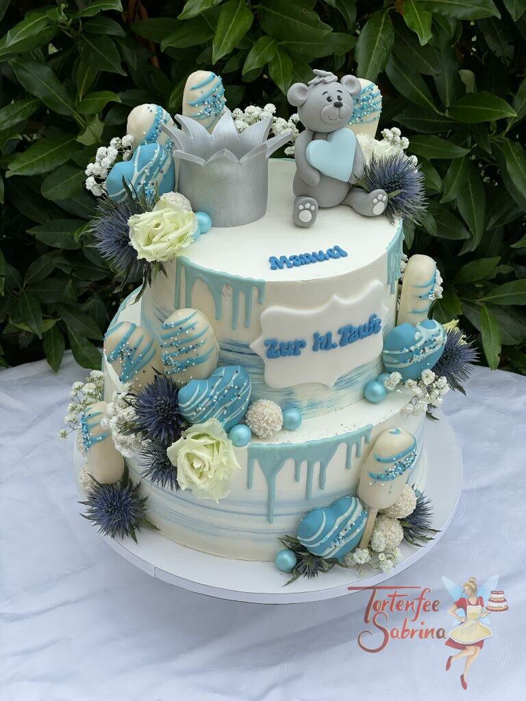 Tauftorte - Bär mit silberner Krone ist ganz oben auf der Torte und hält ein blaues Herz zwischen Blumen und Süßigkeiten.