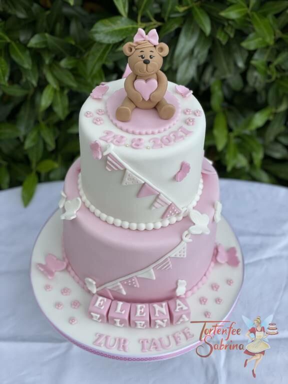 Tauftorte - Bärchen mit Herz und Schleife ganz oben auf der Torte, geschmückt mit einer rose und weißen Wimpelkette.