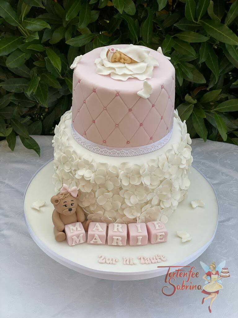 Tauftorte - Blumen und Blüten in der Farbe weiß zieren den unteren Teil der Torte, oben wurde ein Rautenmuster auf die Torte aufgebracht.