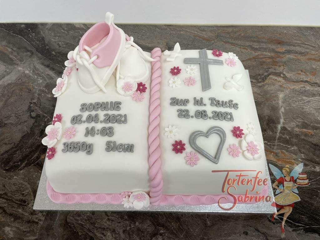 Tauftorte - Buch mit Herz und Kreuz, in der Mitte zierte eine rosa Kordel das Buch. Blumen und Schüchen sind auch noch auf der Torte.