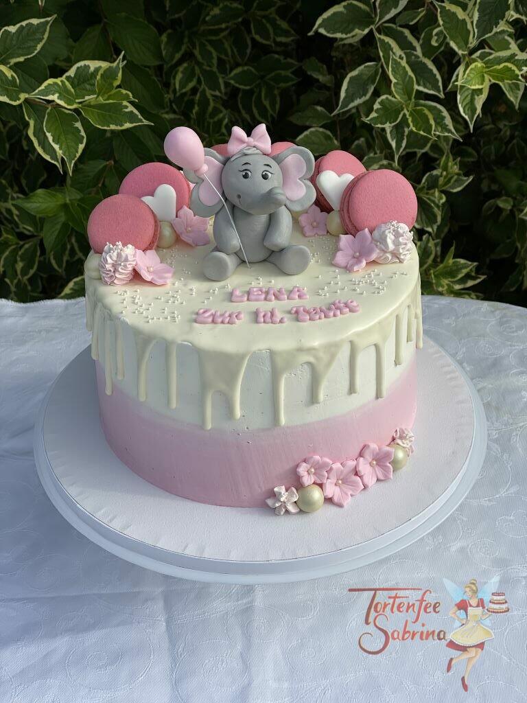 Tauftorte - Elefant mit rosa Luftballon und Schleife sitzt oben auf der Torte zwische Blumen und Süßigkeiten.