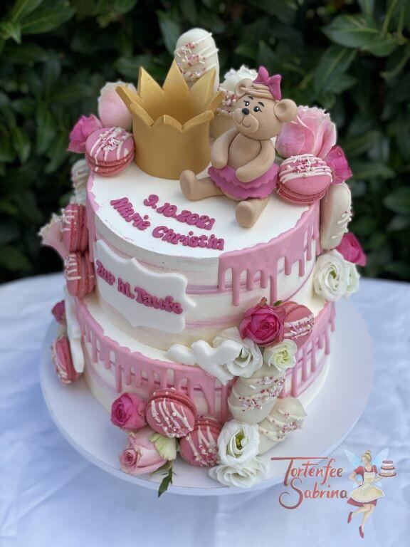 Tauftorte - Goldene Korne und Bärchen mit rosa Schleife sitzen oben auf der Torte umgeben von vielen Süßigkeiten.