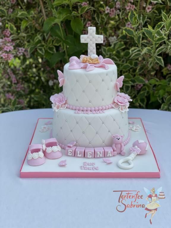 Tauftorte - Kreuz mit Perlen und Baby auf einer Blüte. Auf der Torte sind ebenfalls noch Blumen, ein Kreuz und Babyschuhe.