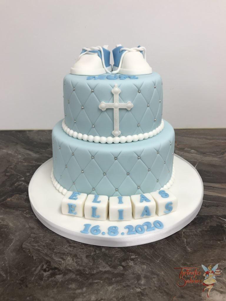 Tauftorte - Schüchen in blau. Die Torte wurde mit einem Rautenmuster und Perlen verziert. Sowie einem Kreuz in weiß und Würfeln mit dem Namen.