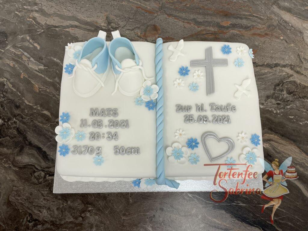 Tauftorte - Taufbuch mit silbernem Herzen und Kreuz, ebenfalls auf dem sind blaue Schüchen und Blumen in den Farben weiß und blau.