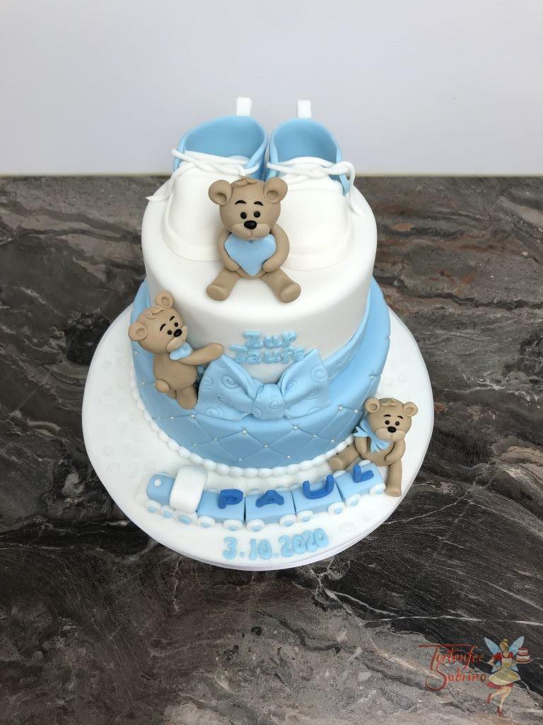 Tauftorte - Teddys mit Zug und blauen Schleifen. Die Torte wurde unten blau eingedeckt und mit einem Rauten- und Perlenmuster verziert.
