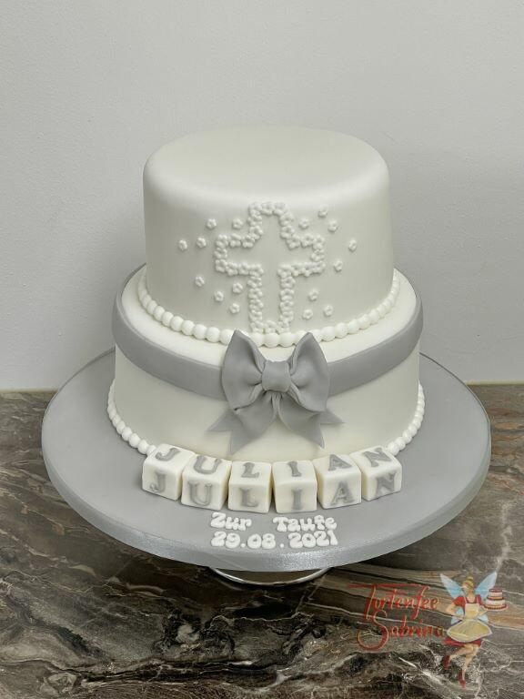 Tauftorte - Weißes Kreuz aus Blumen verziert die Torte oben, darunter ist eine graue Schleife und der Name auf den Würfeln.